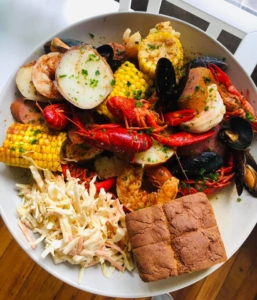 Image of a plate with seafood, veggies, and sides